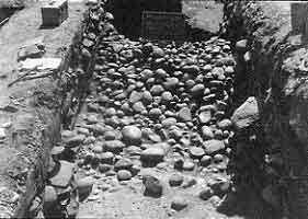 Figure 8.23 View west of wall (Strata V). The first layer of revestimento (glacis) cobbles were removed from Strata III. Fort Guijarros Museum Foundation Photo Collection, P:81-7272.